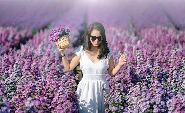 일몰에 라벤더 분야에서 아름 다운 소녀. 놀라운 드레스에 아름 다운 여자는 라벤더의 분야에 걸어.