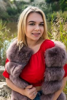 暖かい秋の日に湖のそばでポーズをとる毛皮のコートと明るい赤のtシャツとショートパンツの美しい少女