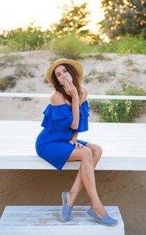 帽子と青いドレスを着た美しい少女が砂浜に座っています
