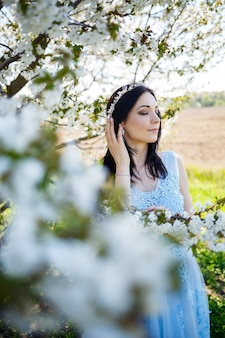 Красивая девушка в легком летнем синем длинном платье, украшенном в волосах, на фоне цветущего дерева. нежный портрет молодой женщины в белом цвете