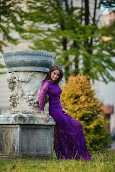 Красивая девушка в роскошном платье гуляет в парке осени около замка. принцесса сидя падения замка. модная тонировка.