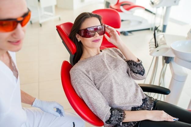 歯科用椅子に医療用眼鏡をかけた美しい少女。