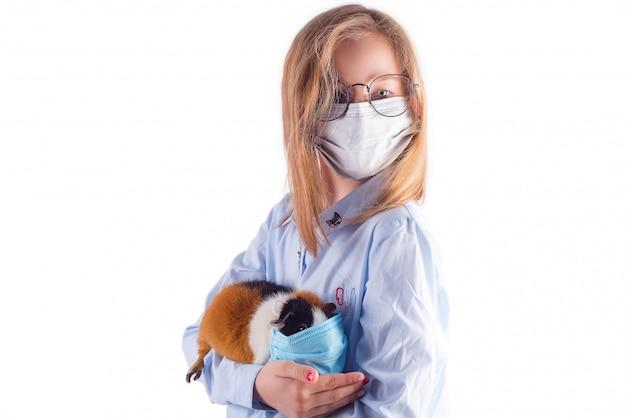 Красивая девушка в медицинской маске и очках держит в руках морскую свинку в защитной маске на светло-сером