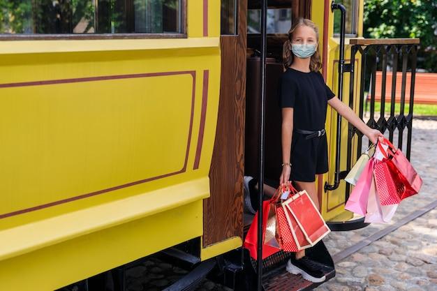 도시에서 컬러 가방을 들고 얼굴에 의료 마스크를 쓴 아름다운 소녀