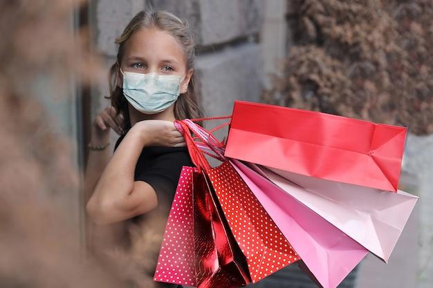 市内のカラーバッグと顔の医療マスクの美しい少女
