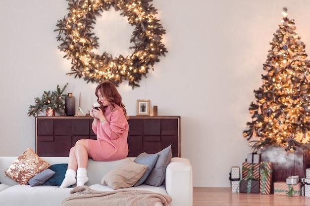 Красивая девушка в розовом свитере и носках сидит на диване с чашкой горячего напитка