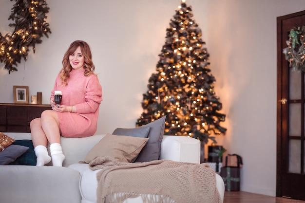 Красивая девушка в розовом свитере и носках сидит на диване
