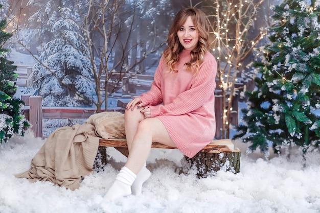 Красивая девушка в розовом свитере сидит в елочных игрушках с искусственным снегом