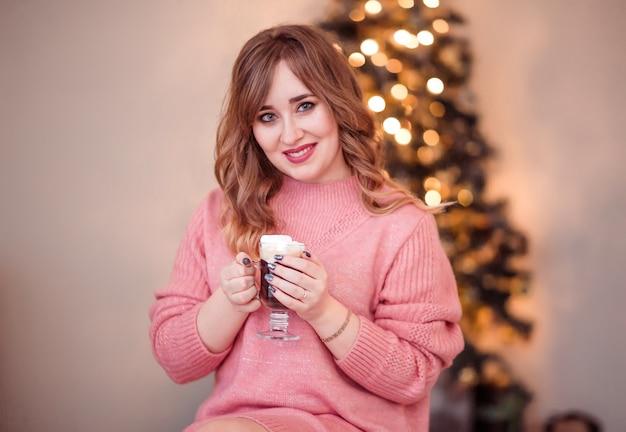 Красивая девушка в розовом свитере с чашкой кофе и зефиром