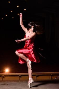 Красивая девушка в красном платье танцует на сцене.
