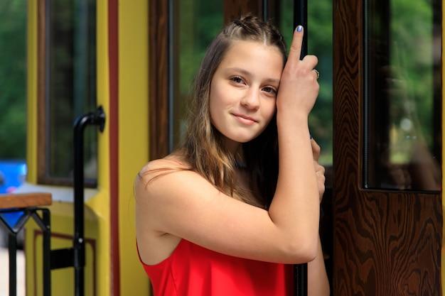 黄色の路面電車で赤いドレスを着た美しい少女