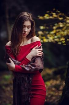 赤いドレス、長い黒髪、アジアの外観を持つ美しい少女が春の公園を歩きます