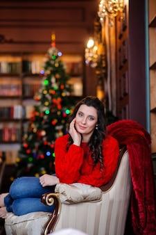 クリスマスツリーの近くの赤いセーターの美しい少女。