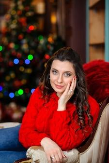 Красивая девушка в красном свитере возле елки