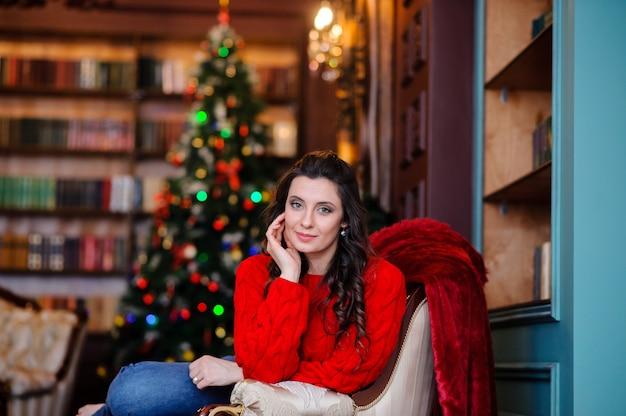 Красивая девушка в красном свитере возле елки.