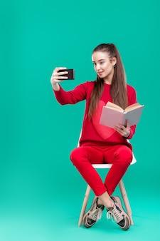 赤いセーターを着た美少女が本を読み、スマートフォンを使って自分撮り