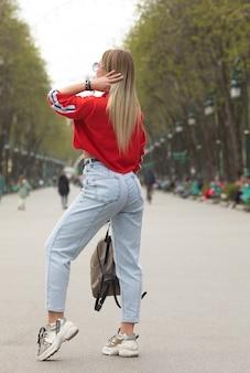 赤いトップハイウエストジーンズウォーキングストリートの美しい少女
