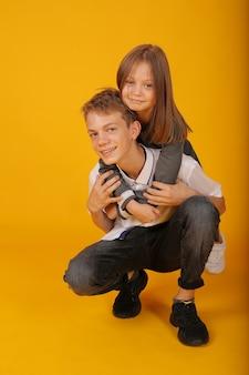 Красивая девушка в школьном платье обнимает своего старшего брата школьника в белой рубашке и брюках