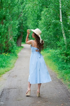 公園の道路で麦わら帽子と青いドレスを着た美しい少女。