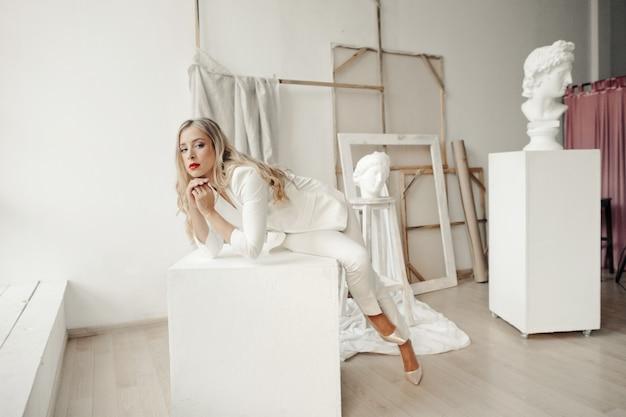 세련된 흰색 정장을 입고 아름다운 소녀는 갤러리에서 흰색 큐브에 앉아