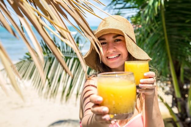 ビーチでヤシの葉の背景に新鮮な飲み物と夏の帽子で美しい少女、女の子は飲み物、クローズアップ、休日の概念を提供しています