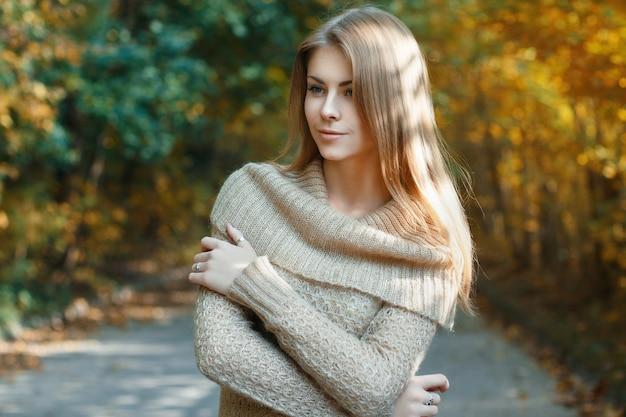 秋の公園に立っているセーターの美しい少女