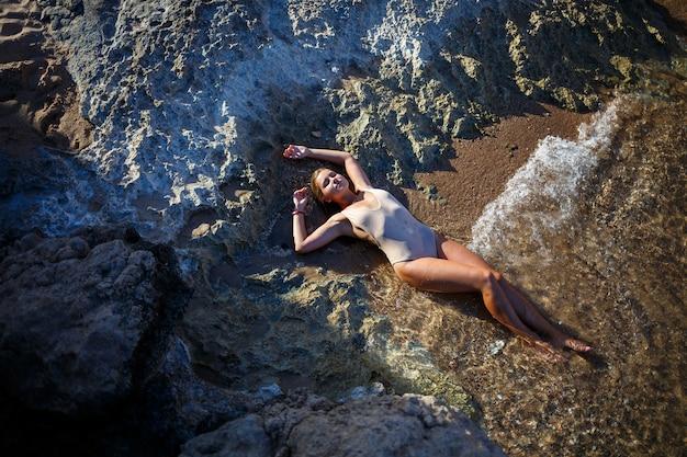 수영복을 입은 아름다운 소녀는 바닷물에 모래 해변에 누워