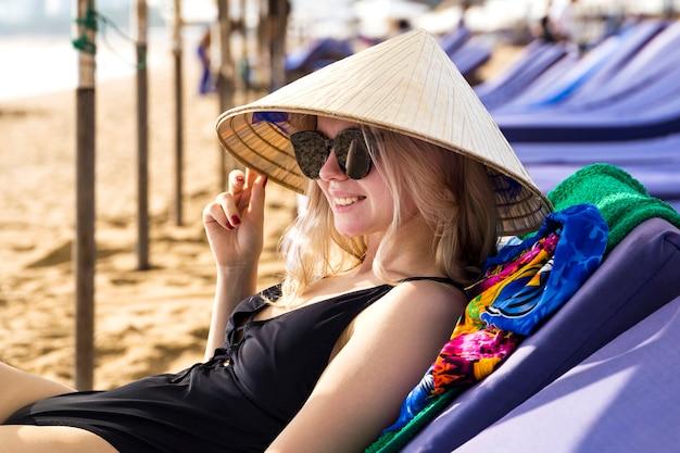 海の近くのビーチに座っている伝統的なアジアの円錐形の帽子で美しい少女