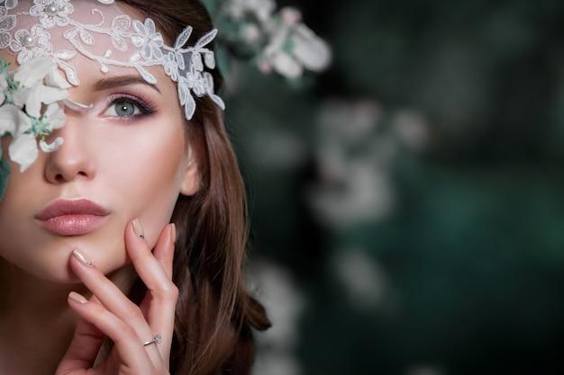 피 정원의 배경에 웨딩 드레스에서 아름 다운 소녀.