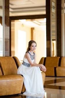 Красивая девушка в белом платье в красивом интерьере.