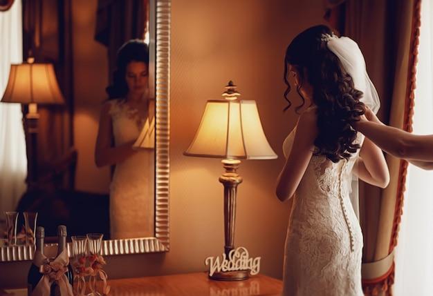 Красивая девушка в белом платье готовится к свадебной церемонии
