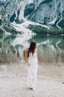 산에있는 호수 근처 하얀 드레스를 입고 아름 다운 소녀.