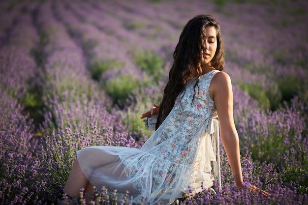 白いドレスを着た美しい少女が木製の椅子に座って、ラベンダー畑の真ん中でポーズをとる、
