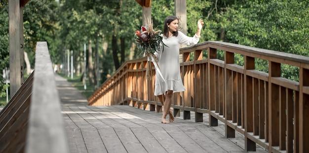 Красивая девушка в белом платье с букетом экзотических цветов на деревянном мосту.