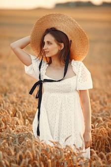 白いドレスを着た美しい少女。秋のフィールドの女性。麦わら帽子の女性。
