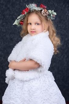 회색 배경에 그녀의 머리에 크리스마스 화환과 흰색 모피 코트에 아름 다운 소녀