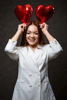 그녀의 손에 빨간 풍선 하트와 흰색 재킷에 아름 다운 소녀