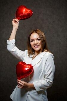 彼女の手に赤い風船の心を持つ白いジャケットの美しい少女