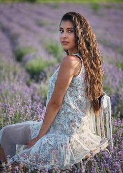白いサラファンの美しい少女は、木製の椅子に座って、ラベンダー畑の真ん中でポーズをとる。