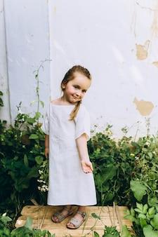 白い壁の背景に緑の芝生の上の白いシャツで美しい少女