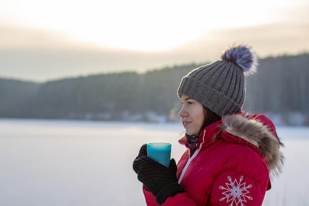 自然の中で冬のマグカップと冬のジャケットの美しい少女。帽子と赤い暖かいジャケットを着た女の子。彼は手を温め、熱いお茶や飲み物を飲みます