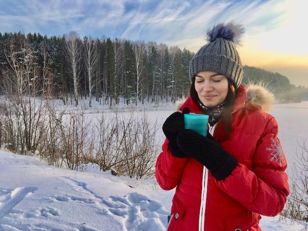 자연 속에서 겨울에 얼굴로 겨울 자 켓에서 아름 다운 소녀. 모자와 빨간색 따뜻한 재킷에 소녀. 그는 손을 따뜻하게하고 뜨거운 차나 음료를 마신다