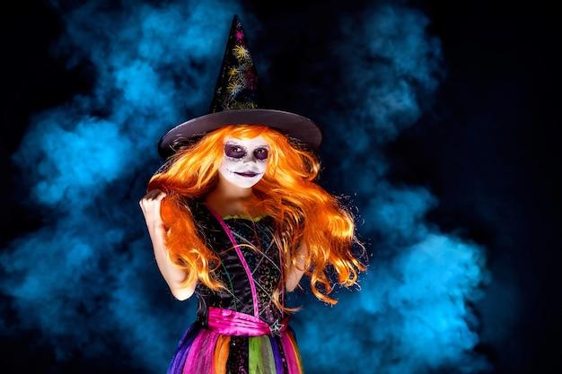 연기에 어두운 배경에 마녀 의상에서 아름 다운 소녀