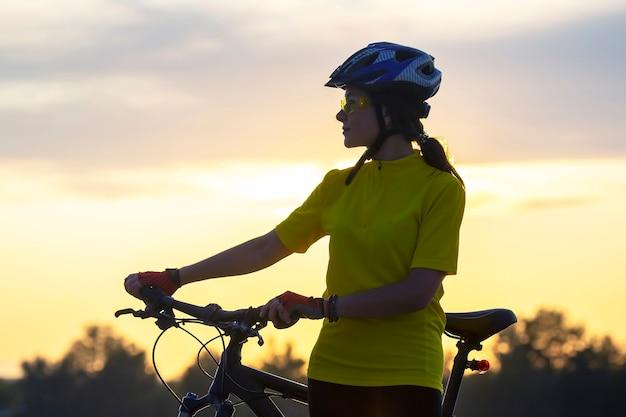 자전거에 노란색 사이클에서 아름 다운 소녀는 햇빛에 도달합니다. 스포츠 및 레크리에이션. 자연과 사람