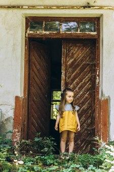 木製のドアの近くの黄色のドレスで美しい少女