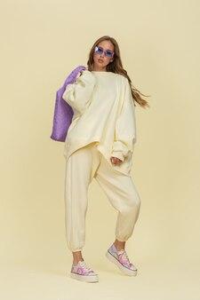 スタジオでフルハイトポーズをとる黄色のスポーツスーツと紫色のアクセサリーの美しい少女