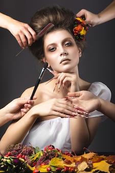 밝고 특이한 메이크업으로 긴 손톱으로 가을 이미지에서 아름 다운 소녀. 회색 배경에 스튜디오에서 찍은 사진