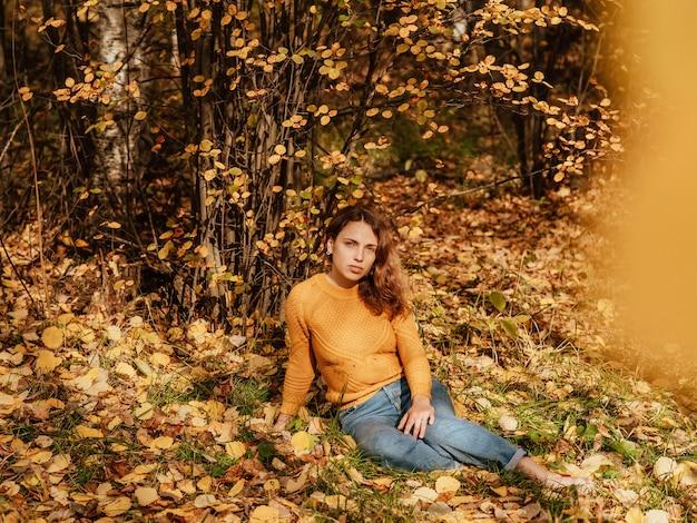 Красивая девушка в осеннем парке, сидя на опавших листьях