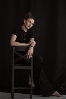 검은 옷에 아름 다운 소녀입니다. 어두운 방에서 매력적인 중년 여자의 초상화.
