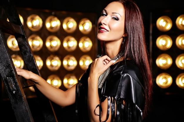 スタジオライトでポーズ黒い服で美しい少女